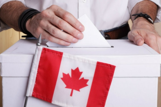 A mans hands dropping a ballot into a ballot box with a Canadian flag in front
