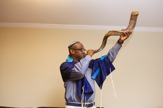 blowing shofar in a blue tallit