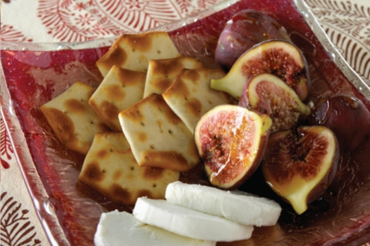 Red plate with crackers and fresh figs and cheese