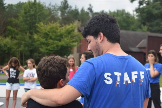 A mans back wearing a blue STAFF shirt with his arm around a young camper