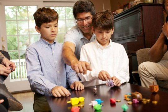 Father and two sons playing dreidel on a wooden table