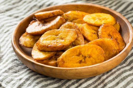 Wooden bowl of fried sweet plantains on a striped grey and white tablecloth