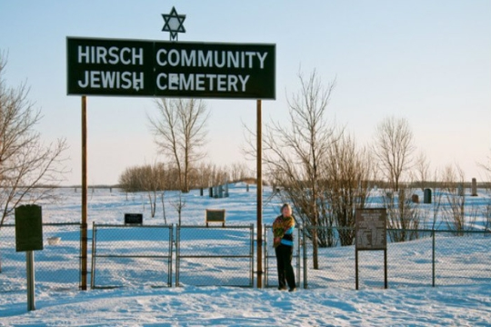 A smiling woman in the snow in front of a large sign reading HIRSCH COMMUNITY JEWISH CEMETERY