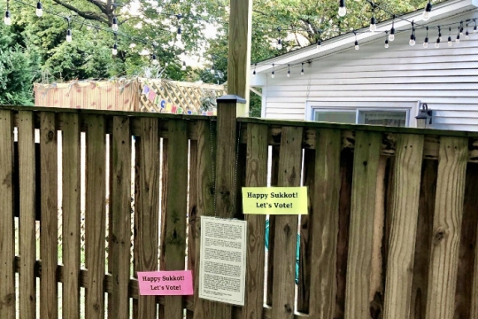 Fence with a printed letter on it and two signs reading ITS SUKKOT LETS VOTE with a sukkah and house visible in the background