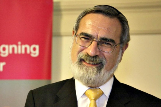 Smiling image of Rabbi Jonathan Sacks wearing a black jacket with a yellow tie