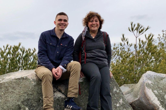 The author sitting on a mountain rock next to the young man who rescued her