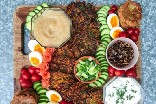 Latke board featuring two kinds of latkes with sour cream applesauce and other toppings