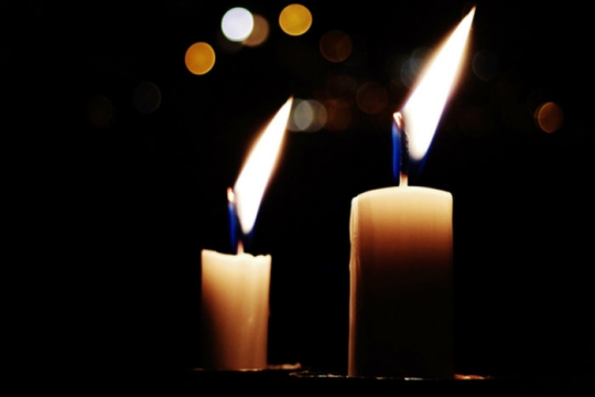 Two Shabbat candles glowing in the darkness