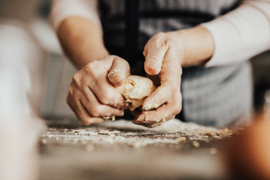 Womans hands kneading dough