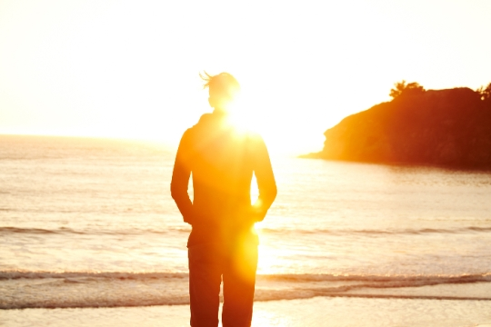 Silhouette of an unidentifiable person standing on a beach at sunset obscured by a sunbeam