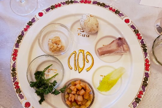 Closeup of a white seder plate with a colorful rim set upon a white tablecloth