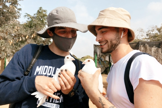 Two men holding doves in their hands while wearing bucket hats