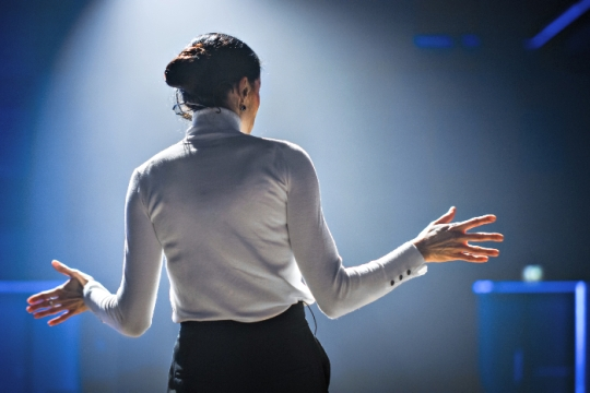Woman in a white turtleneck with her back to the camera and her hands up as if speaking to an audience