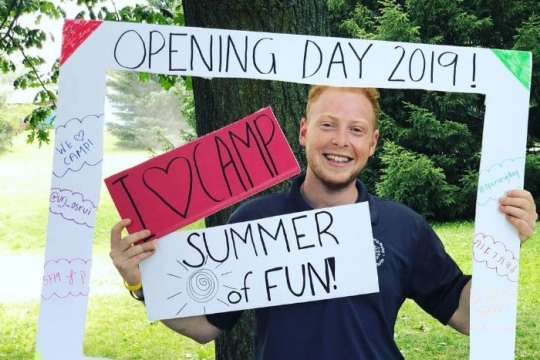 Smiling young man standing in a life sized picture frame that says OPENING DAY 2019