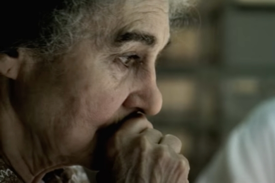 Lynn Cohen with her face in her hands as Golda Meir in a scene from Steven Spielbergs 2005 film Munich