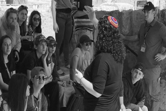 Black and white image of Cantor Katie Oringel teaching students outdoors in Israel with only her rainbow kippah appearing in color