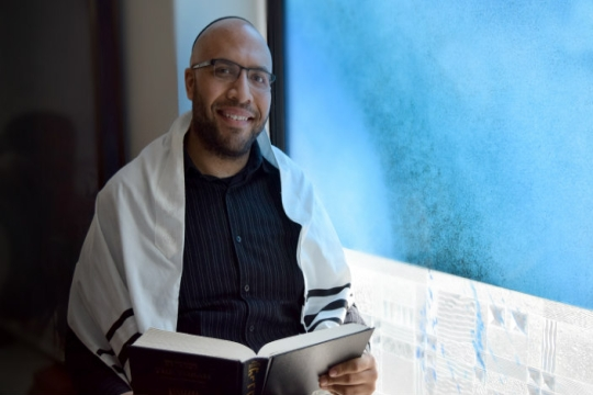 A young black man wearing a prayer shawl and a head covering while reading from a Jewish prayer book