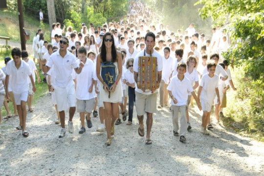 Campers in white being led along a gravel path by two counselors carrying Torah scrolls