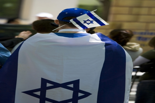 A young boy wearing an Israeli flag as a cape