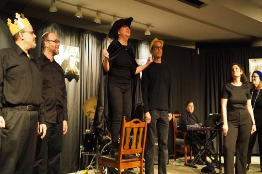 Individuals dressed in all black costumes acting out the Purim story on a small stage