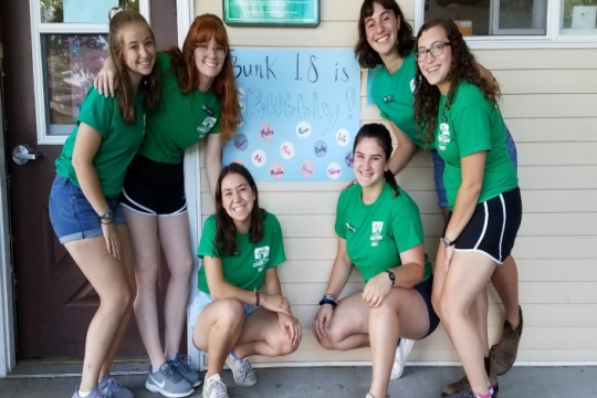 Smiling camp staffers pose in front of a bunk sign