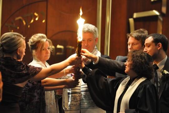 Jewish congregants practicing the candle lighting ritual of Havdallah