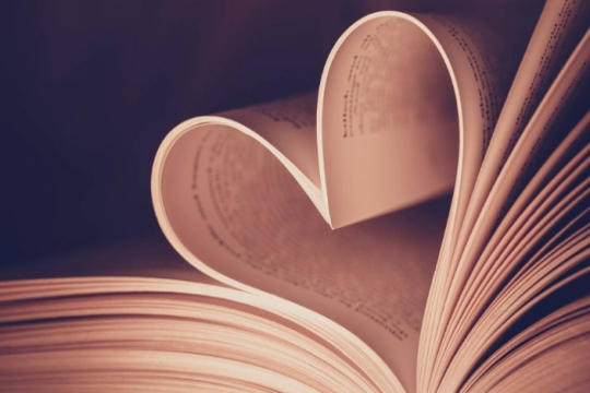 Close up of a book with a turned page formed into the shape of a heart