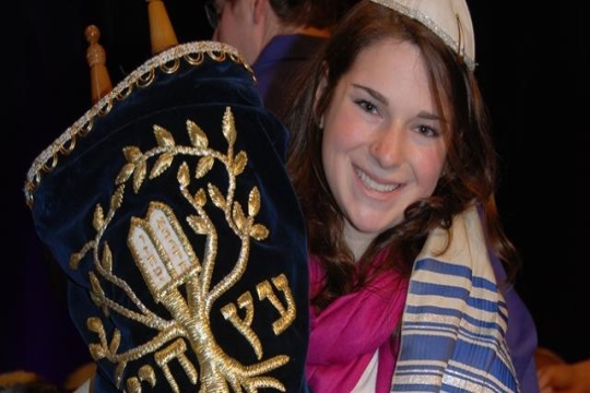 a girl holding up a Torah during her Bat Mitzvah