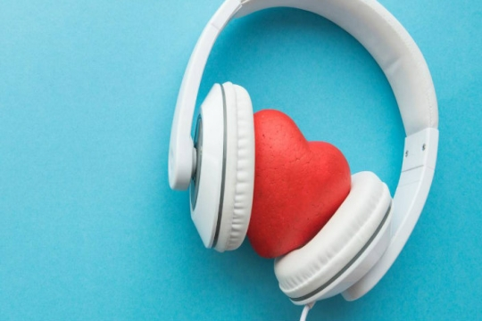 White headphones around a plastic heart against a bright blue background