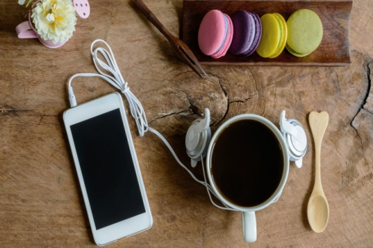 Cell phone with earbuds, coffee, wooden spoon with a heart handle and four pastel macaroons all seen from above