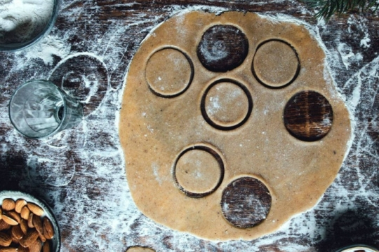 Flattened dough with circular holes cut into it as if making cookies