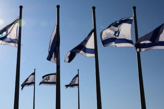 A few Israeli flags on flagpoles against a blue sky background