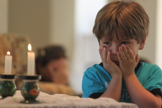 A child praying over candles for the Jewish holiday of Shabbat