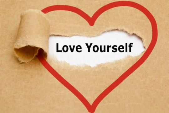 Red outline of heart shape on butcher paper; in the heart, the paper is torn back to reveal the words Love Yourself