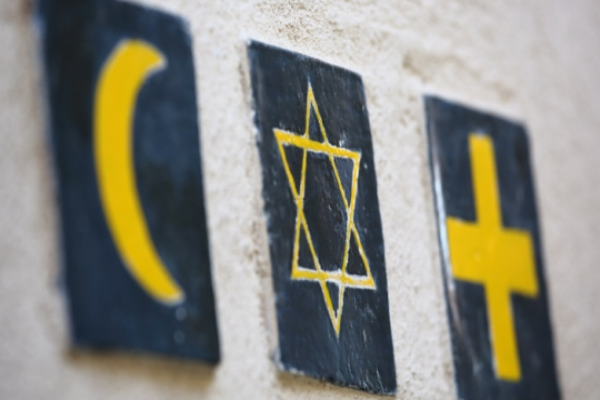 Three seperate tiles on an adobe wall representing three religions: Islam, Judaism, Christianity