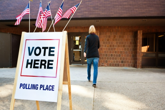 VOTE HERE sign outside a polling place where a women is walking through the doors