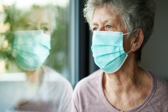 Older woman staring out a window while wearing a face mask