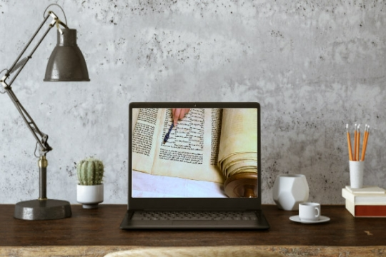 Home desk setup with Torah study displayed on the screen