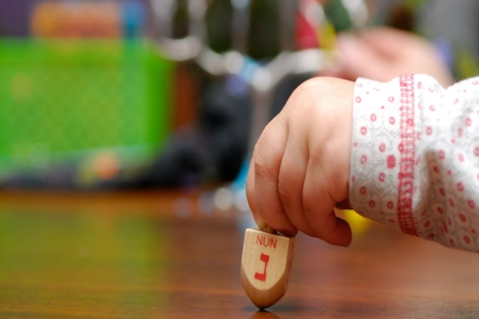 A toddler's hand holding a dreidel in the foreground; hanukkiyah and gifts in the background (blurred)