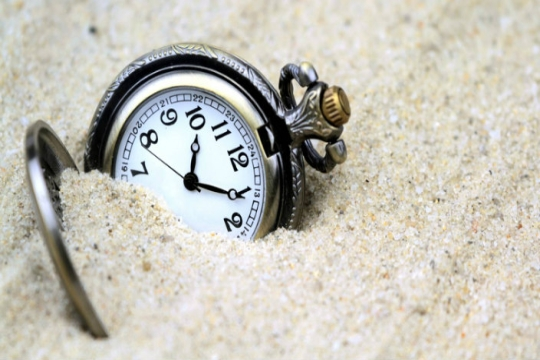 Timepiece partially buried in sand