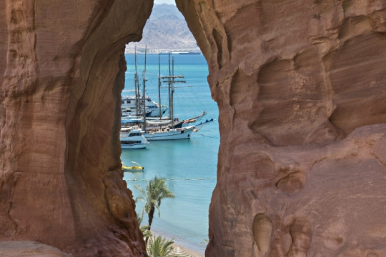 View through a rock formation of water and boats