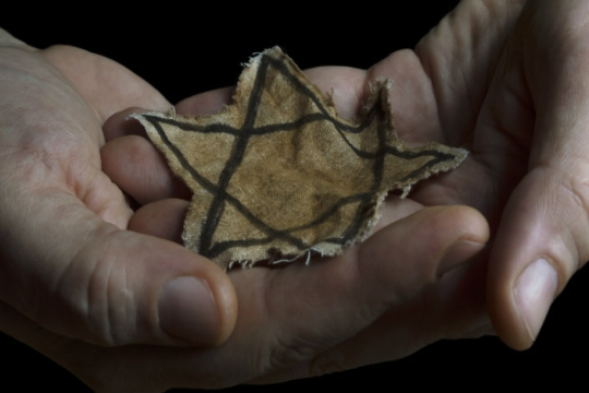Hands holding a yellow fabric star like the one worn by Jewish victims of the Holocaust