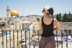 Woman standing on a balcony overlooking the Western Wall and Jerusalem