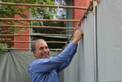 Smiling man tying the sides onto a sukkah