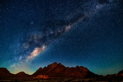 Starry night sky above desert geography
