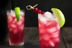 Red drink in a glass with ice cubes and a lime wedge garnish