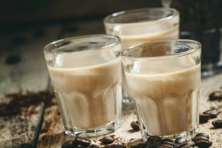 Beige liquid in three small shot glasses surrounded by coffee beans