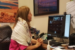 The author sits at her home office while wearing a prayer shawl and speaking on a Zoom call