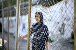 Blurry image of a teenage boy with his hand at a metal fence