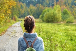 view of woman from the back on an asphalt nature trail